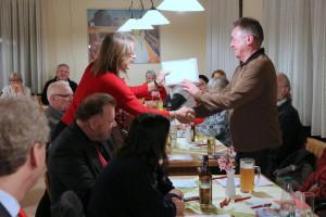 Einem neuen Mitglied wird das Parteibuch überreicht